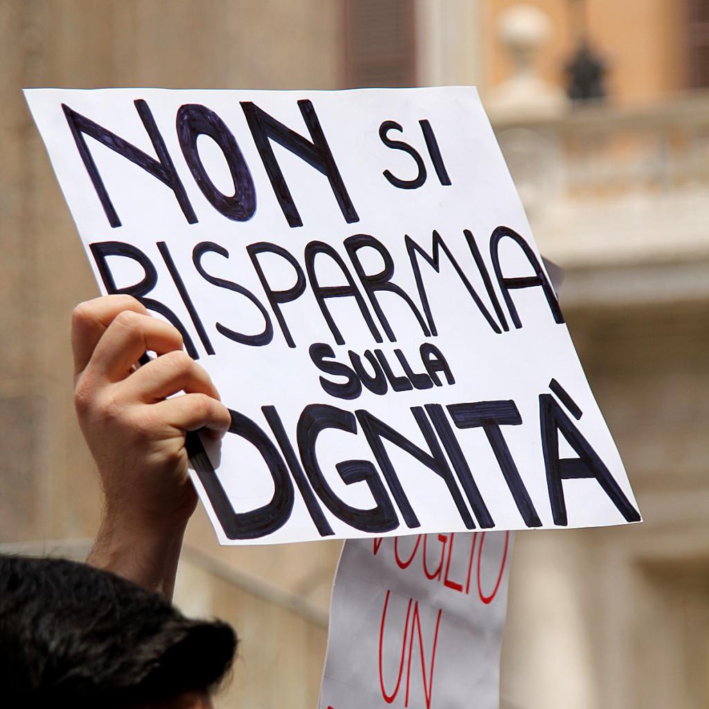 """Manifesto """"Non si risparmia sulla dignità"""" esibito durante la protesta a piazza Montecitorio"""