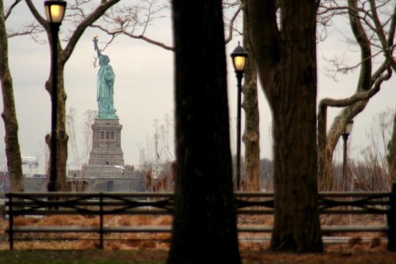 La Statua della Libertà tra gli alberi di Battery Park
