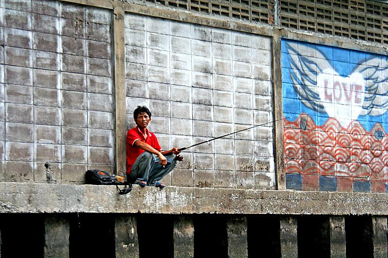 Pescatore lungo un canale di Bangkok
