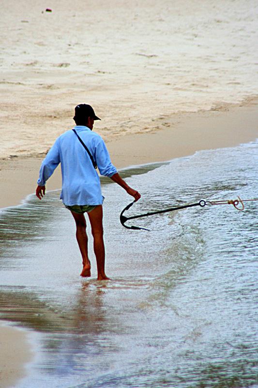 Marinaio ormaggia una barca su una riva di Koh Phangan