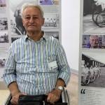 Aroldo Ruschioni in posa davanti ai pannelli della mostra fotografica